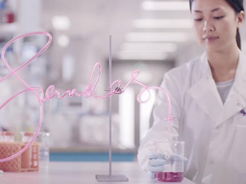 Lab technician hold glass beaker in lab