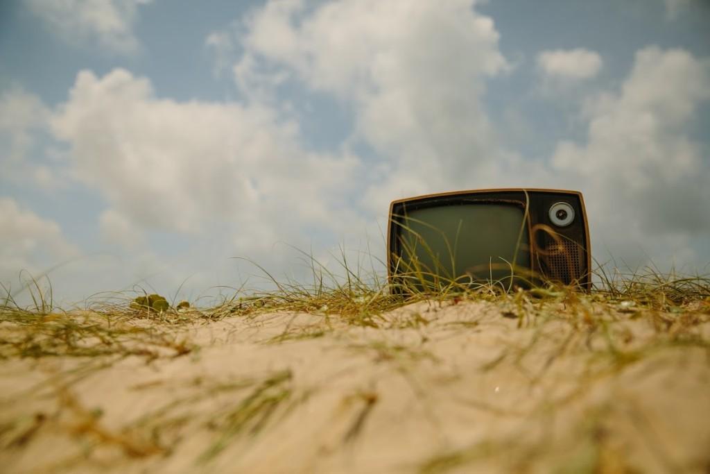 Retro TV in sand dune cloudy sky